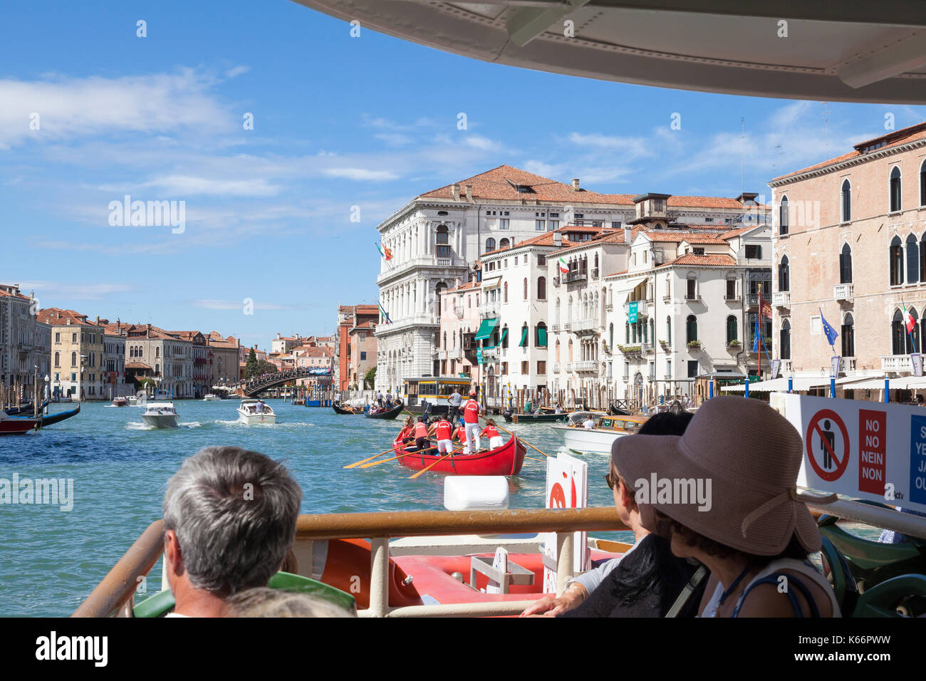 Tourists on a Vaporetto travelling up the Grand Canal, Venice, Italy from a first person point of view looking over the bows. Team of Venetian rowers  - Stock Image
