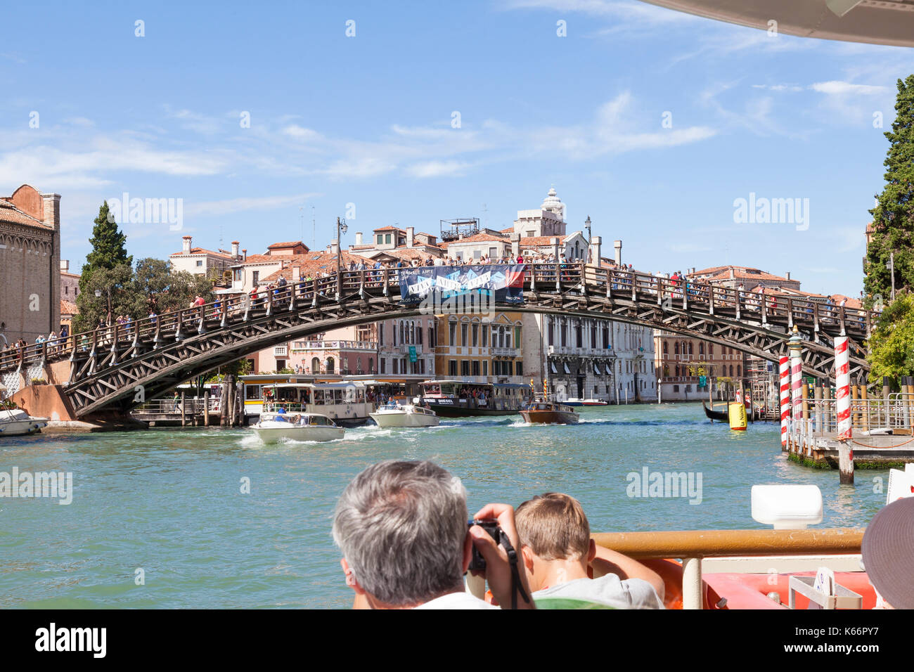 Tourists on a vaporetto travelling up the Grand Canal, Venice, Italy from a first person point of view onboard looking over the bow at the Accademia B - Stock Image