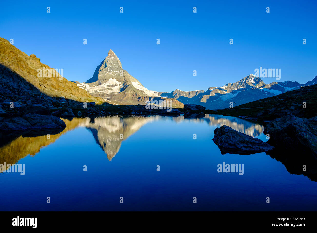 The East Face of the Matterhorn, Monte Cervino, mirroring in the Lake Riffelsee at sunrise - Stock Image