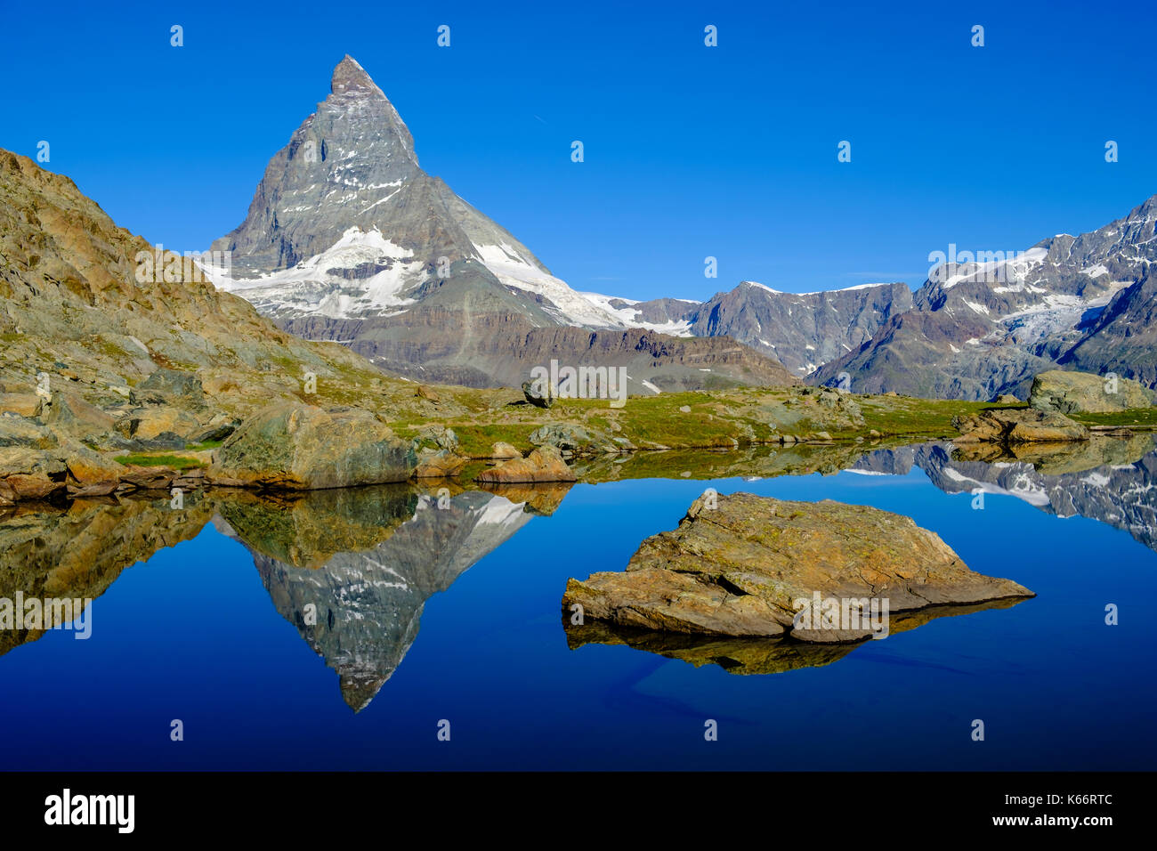 The East Face of the Matterhorn, Monte Cervino, mirroring in the Lake Riffelsee at sunrise Stock Photo