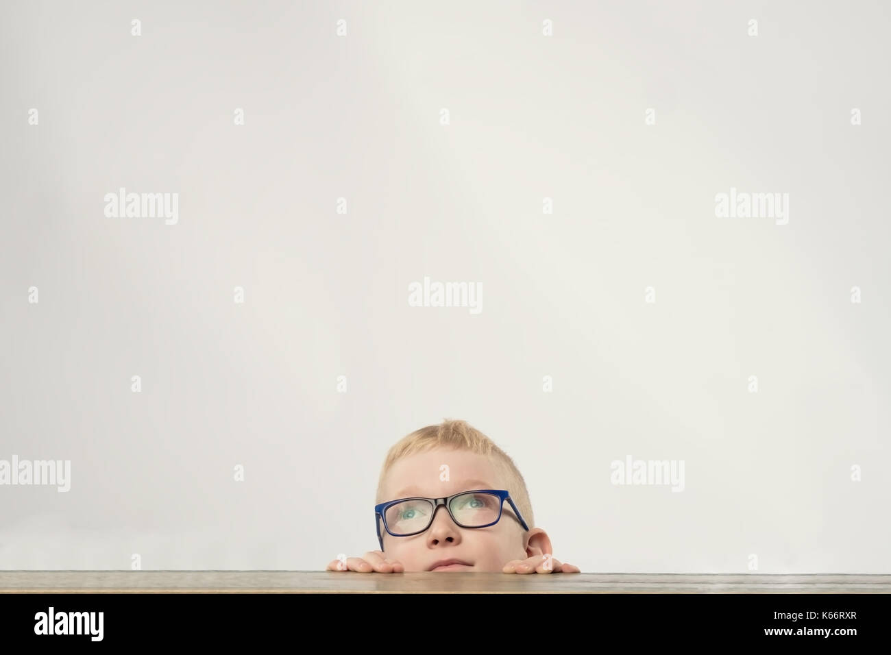 Lovely caucasian boy in glasses hiding and looking up - Stock Image
