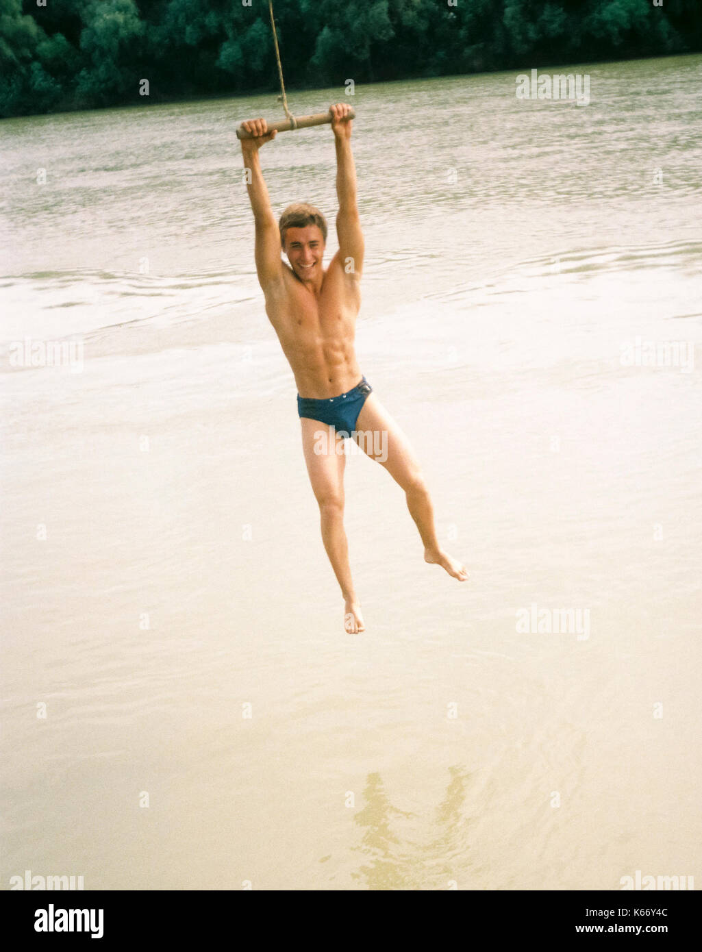 The man is swinging on the tarp. Jumping from the stream on the river bank Stock Photo