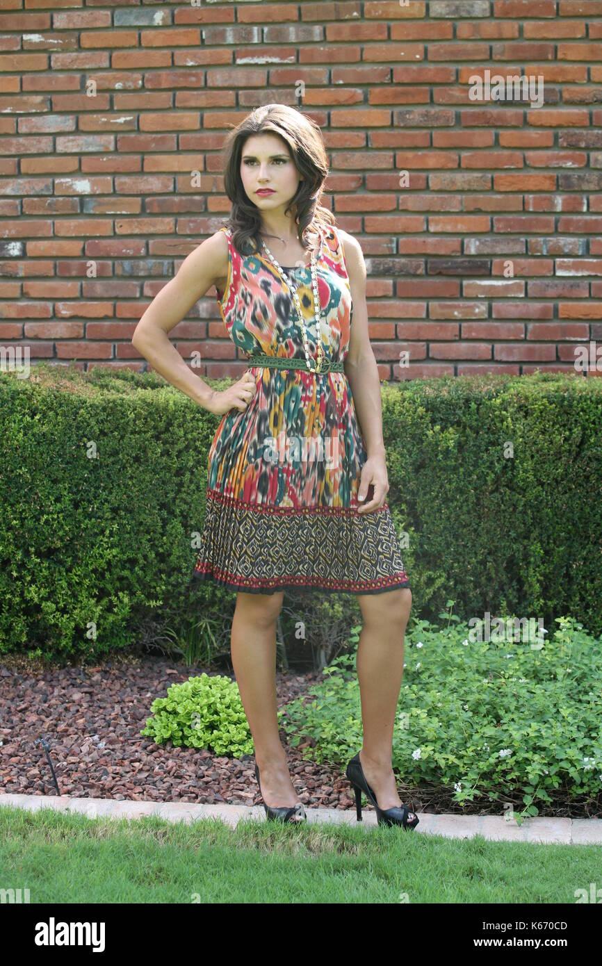 Brunette woman in patterned mini dress - Stock Image
