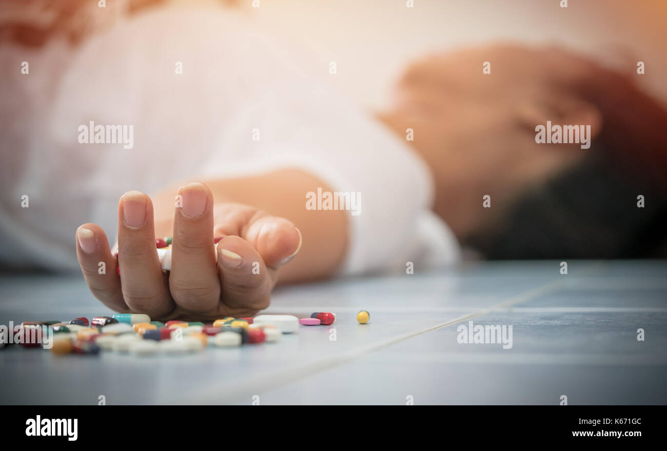 Overdose - close up of pills and addict lying on the floor - Stock Image
