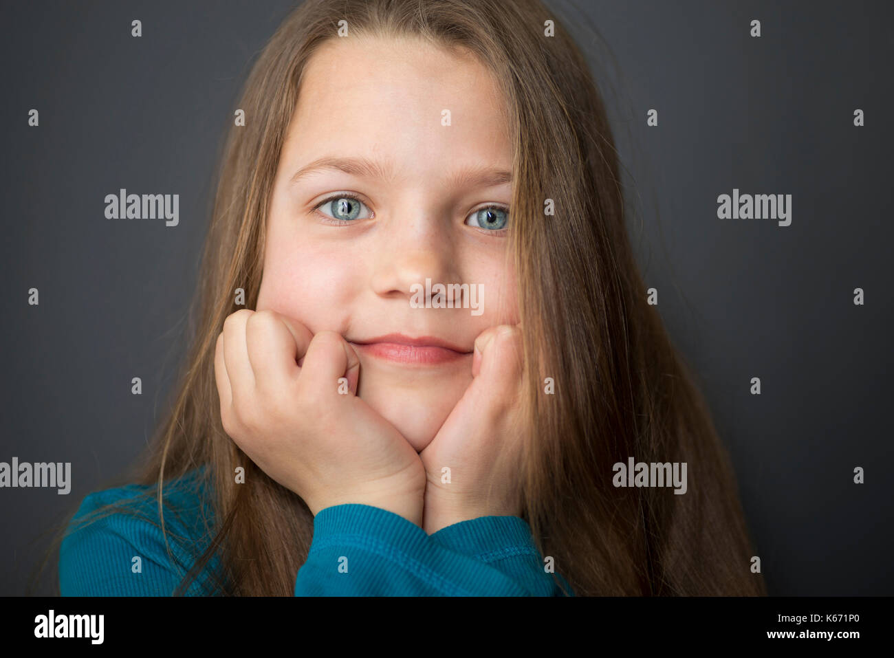 girl with wide open eyes keeping head on hands - Stock Image