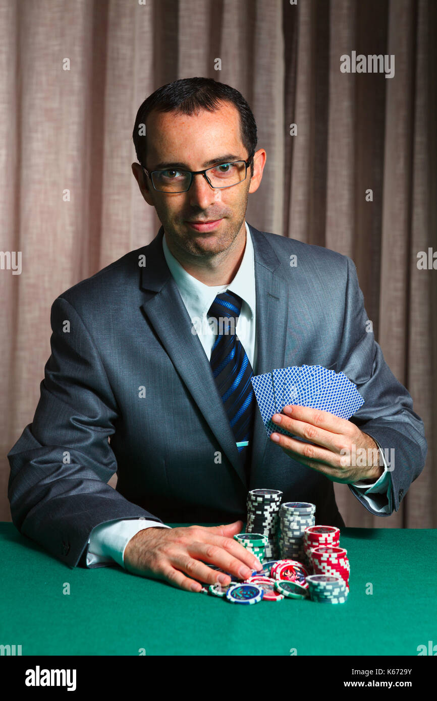 Blackjack in a casino, a happy bussinesman makes a bet, and puts a chip - Stock Image