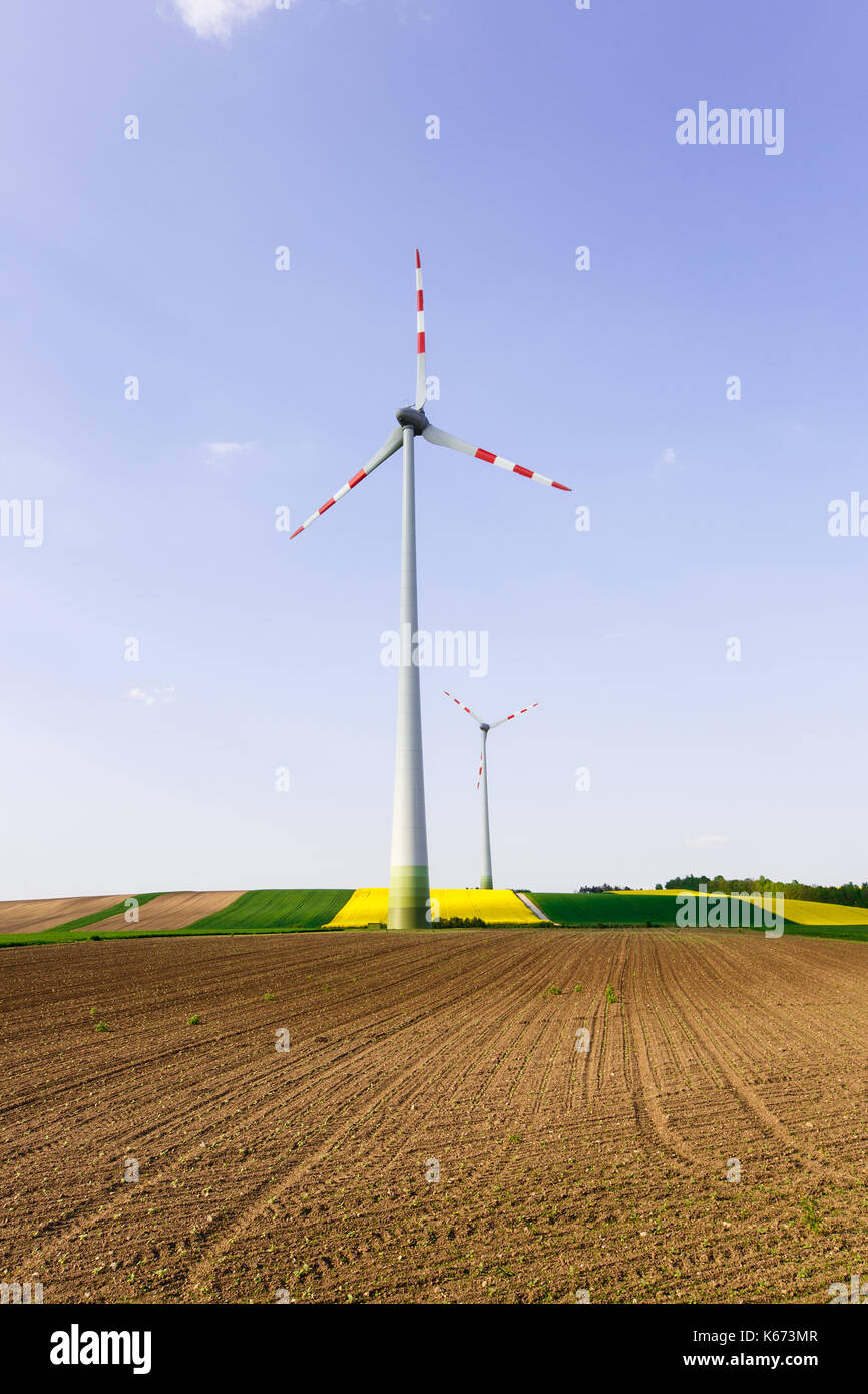 Wind farm with spinning wind turbines amidst agricultural land of intensive crop production. Sustainable and renewable power production, ecology and e - Stock Image
