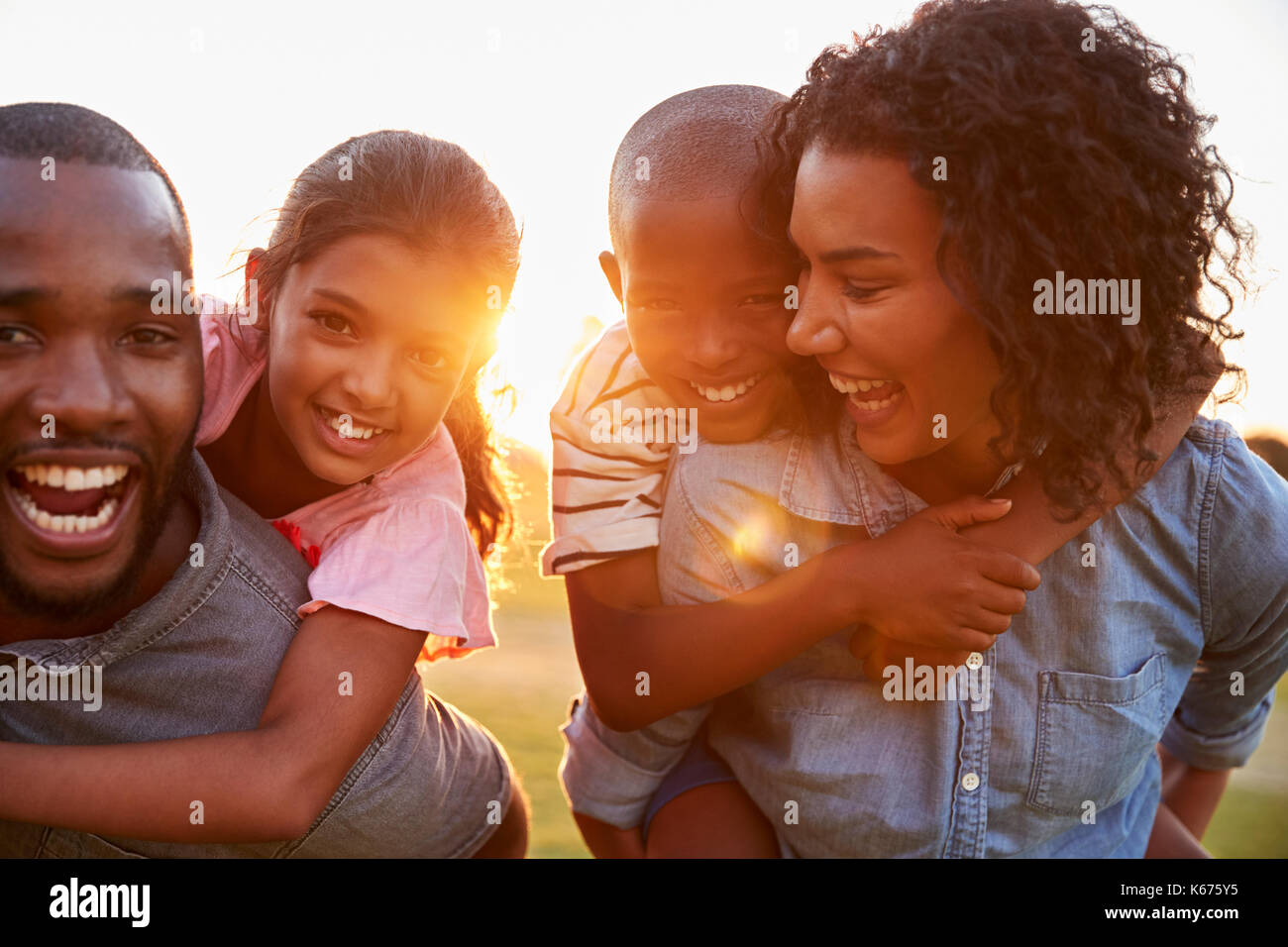 Young black couple enjoying family time with children - Stock Image