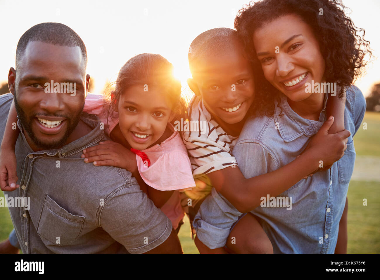 Young black couple with children on piggyback - Stock Image