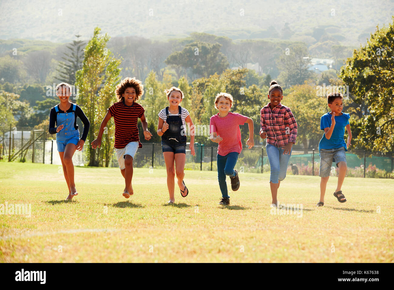 Six pre-teen friends running in a park, front view - Stock Image