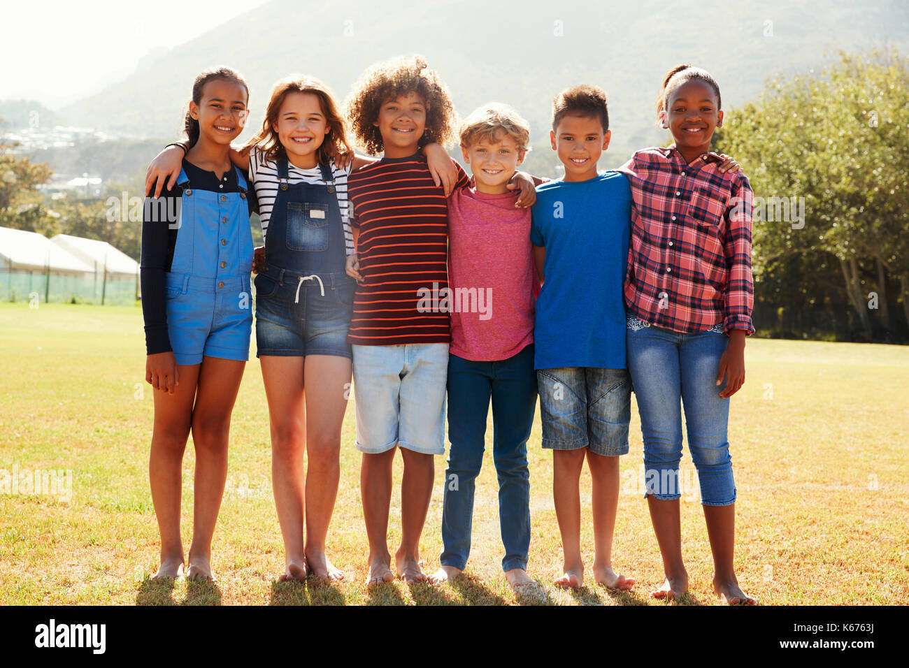 Full length portrait of six pre-teen friends in a park - Stock Image