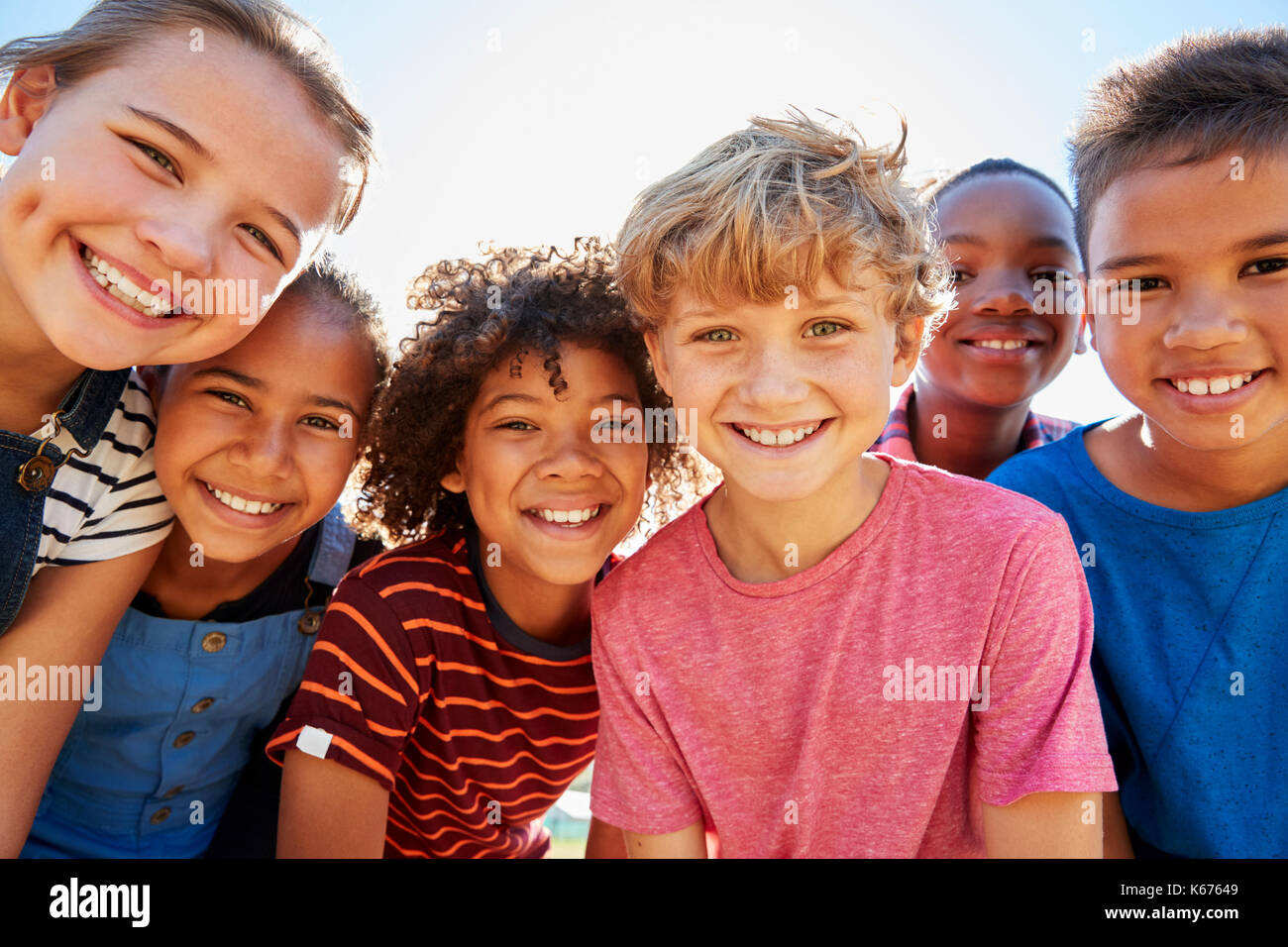 Close up of pre-teen friends in a park smiling to camera - Stock Image