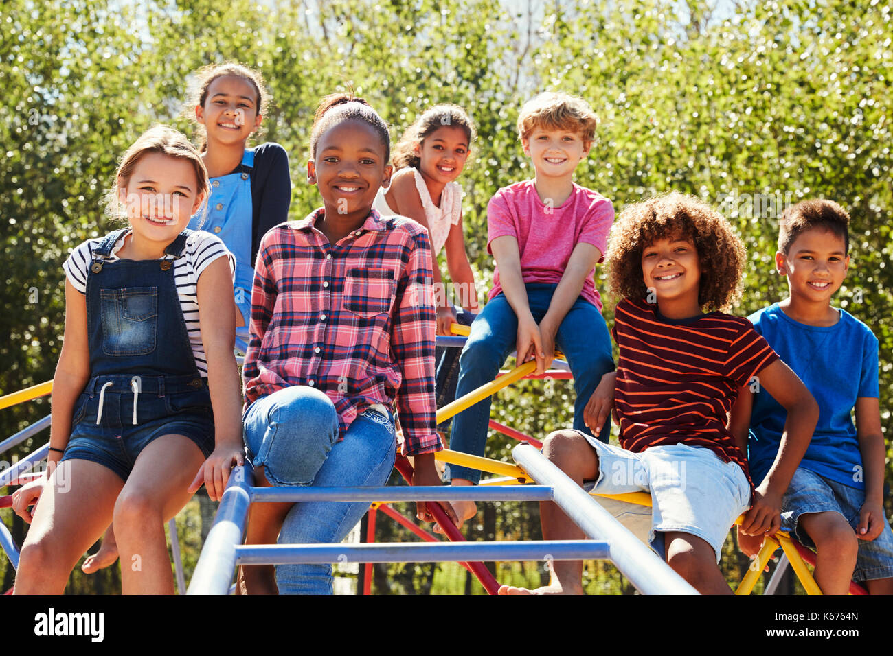 Pre-teen friends sitting on climbing frame in playground - Stock Image