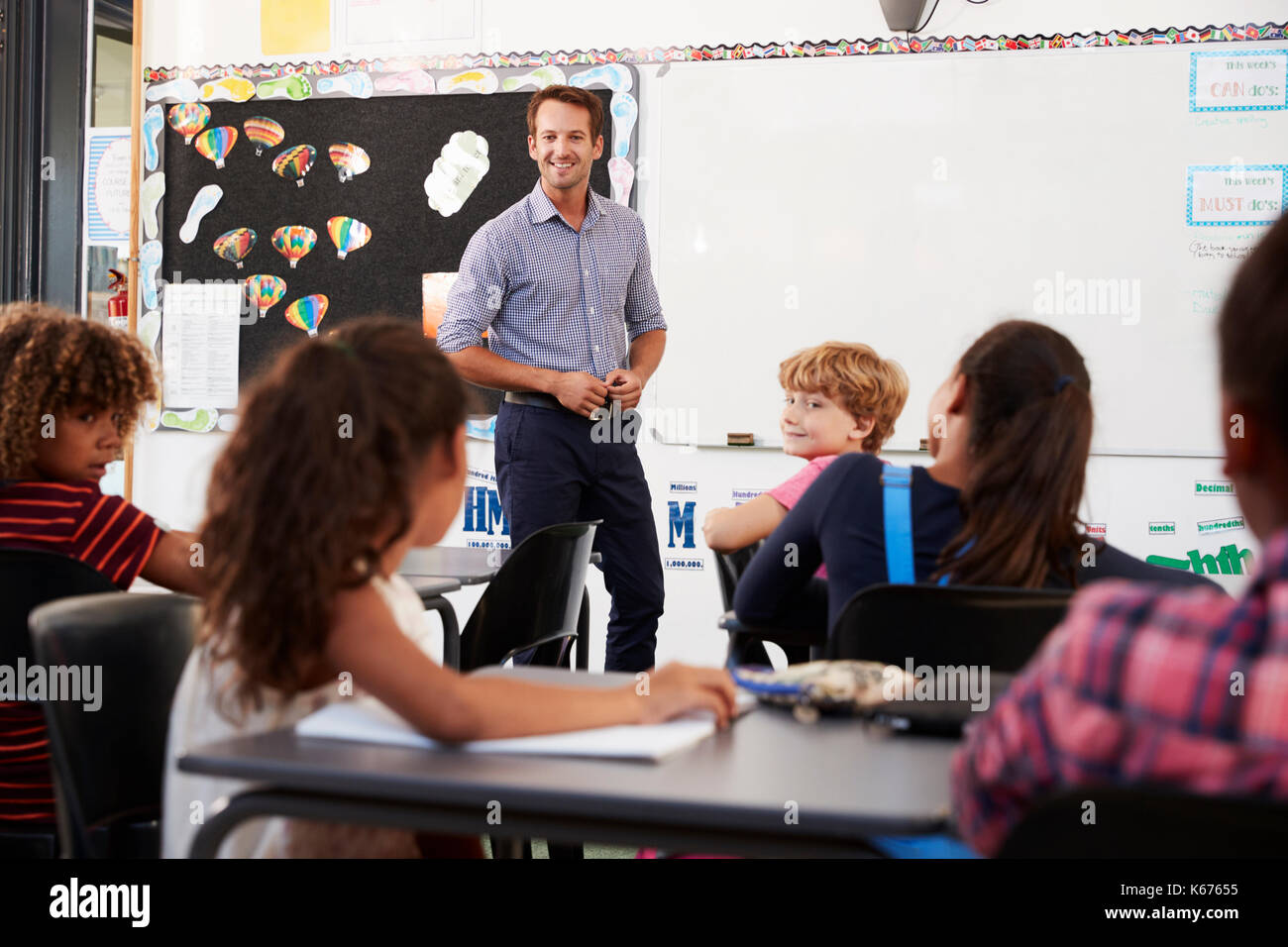 Smiling teacher at front of elementary school class - Stock Image