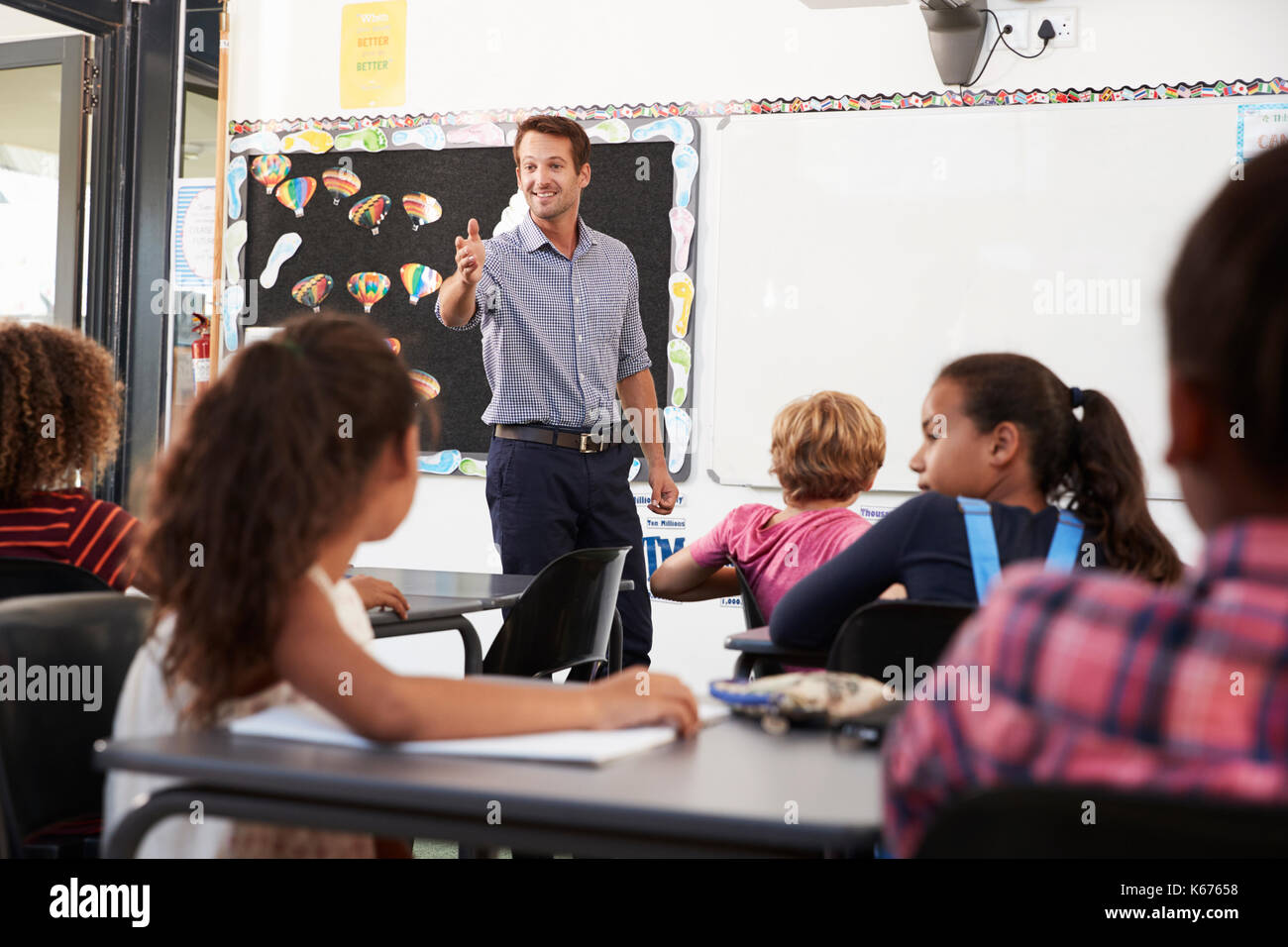 Teacher gesturing to class in an elementary school lesson - Stock Image