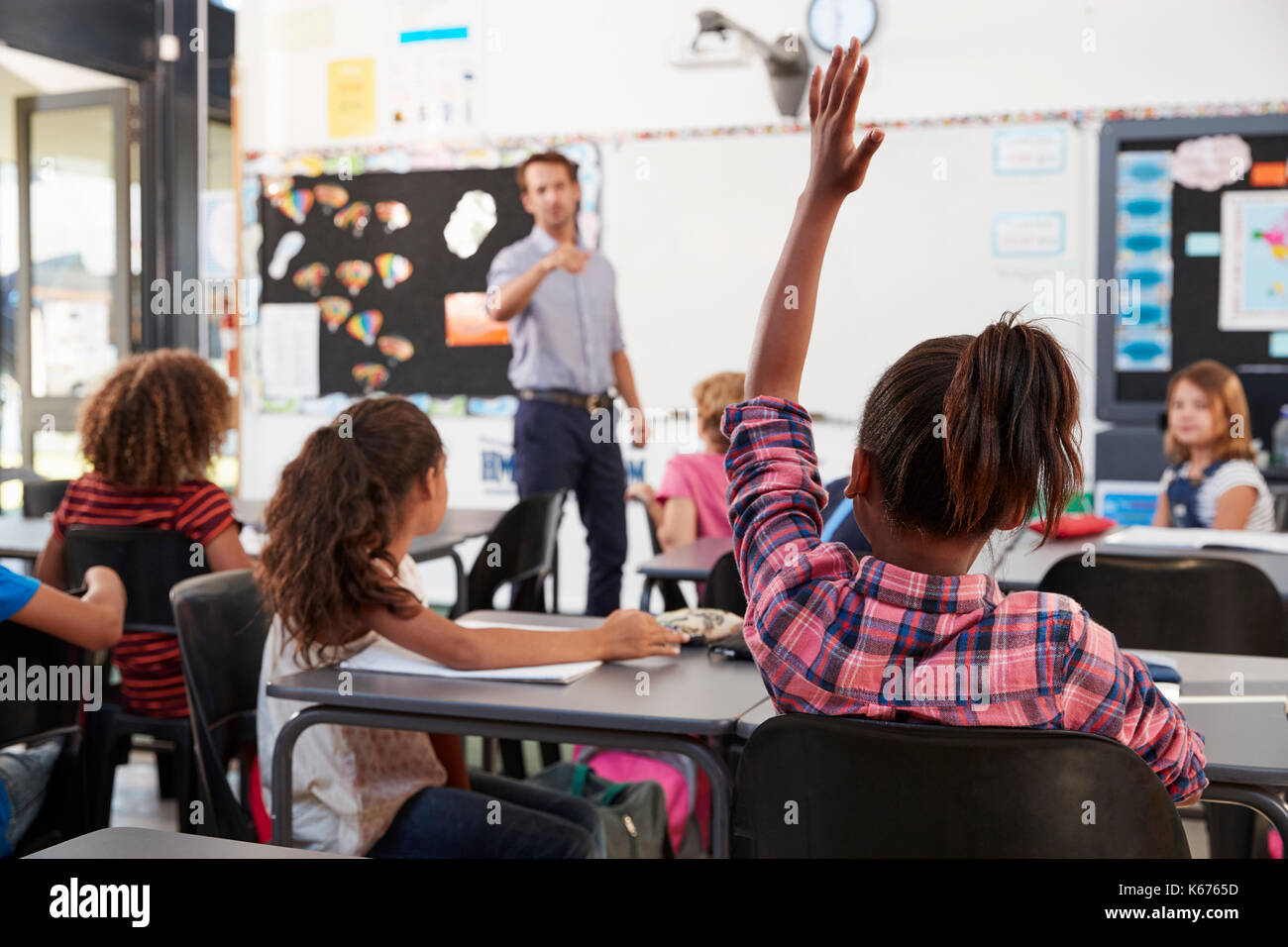 Teacher pointing to elementary school student in class - Stock Image