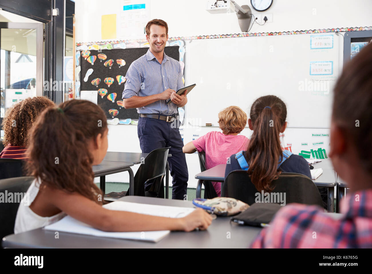 Teacher with tablet in front of elementary school class - Stock Image