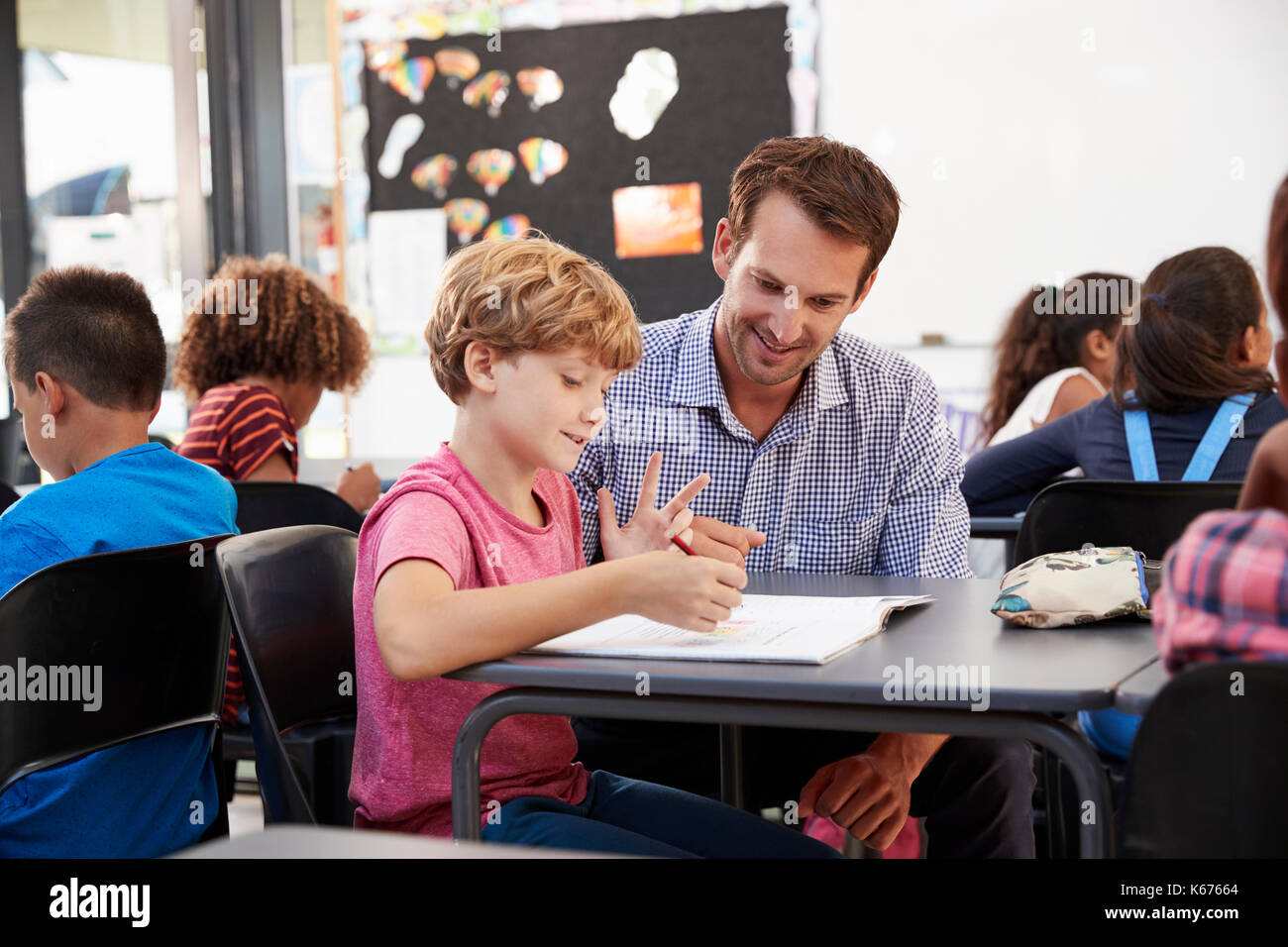 Teacher and young school boy looking at notebook in class - Stock Image