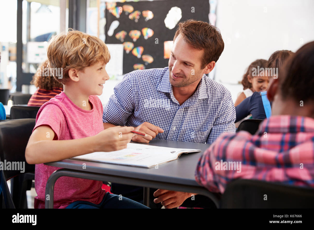 Teacher and long schoolboy at his desk looking at each other Stock Photo