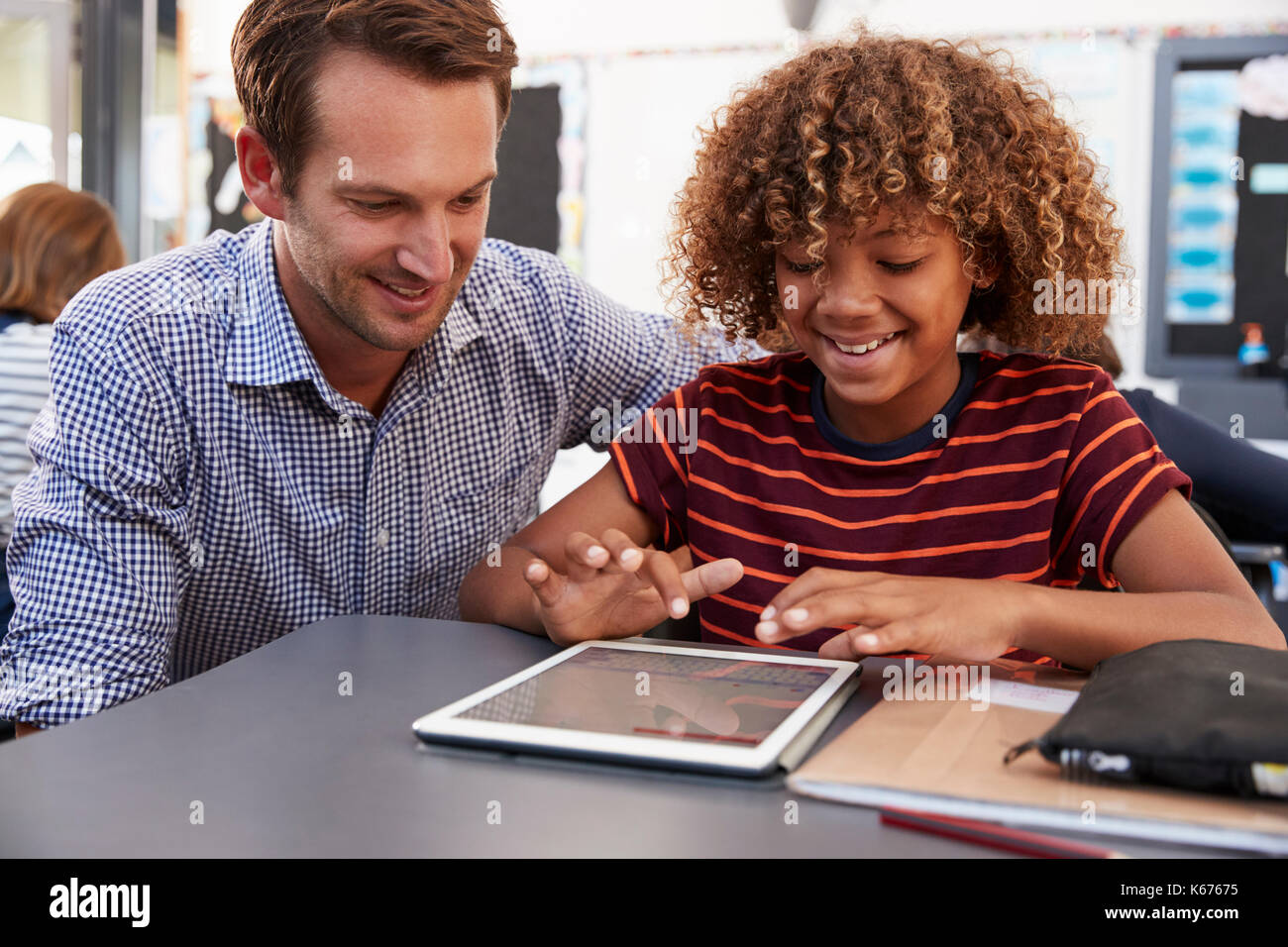 Teacher and schoolboy using tablet computer in class - Stock Image