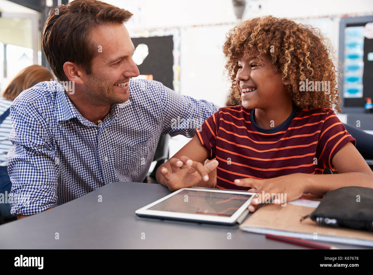 Teacher and schoolboy with tablet looking at each other - Stock Image