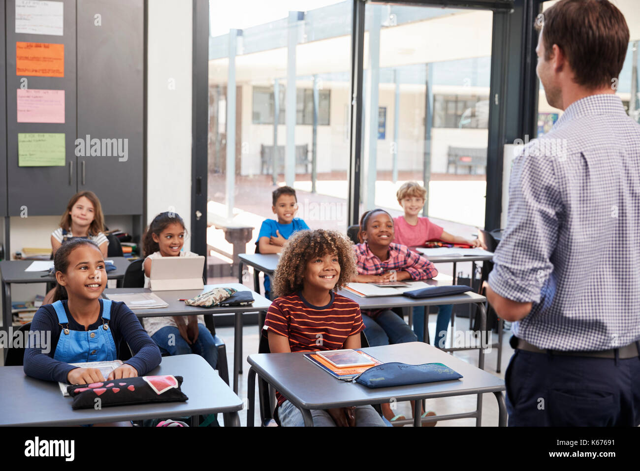 Teacher in front of elementary school class, back view - Stock Image