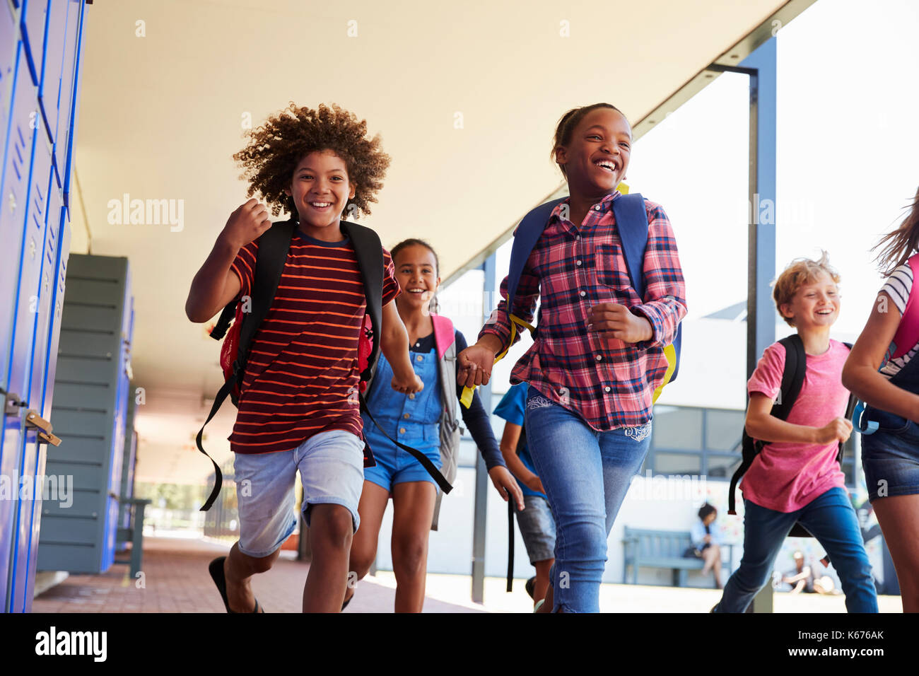 School kids running to camera in school hallway, close up - Stock Image