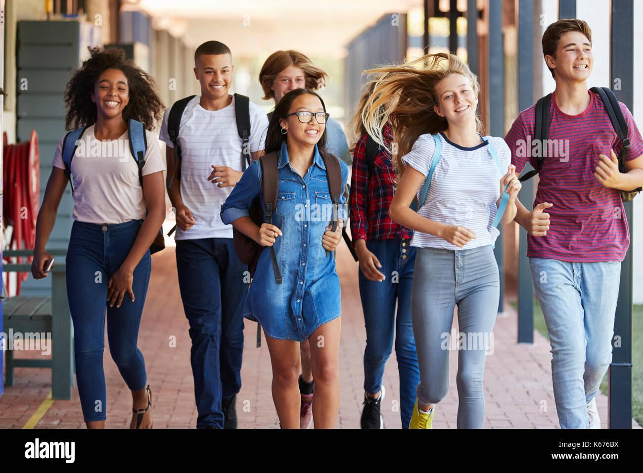 Teenager school kids running in high school hallway - Stock Image