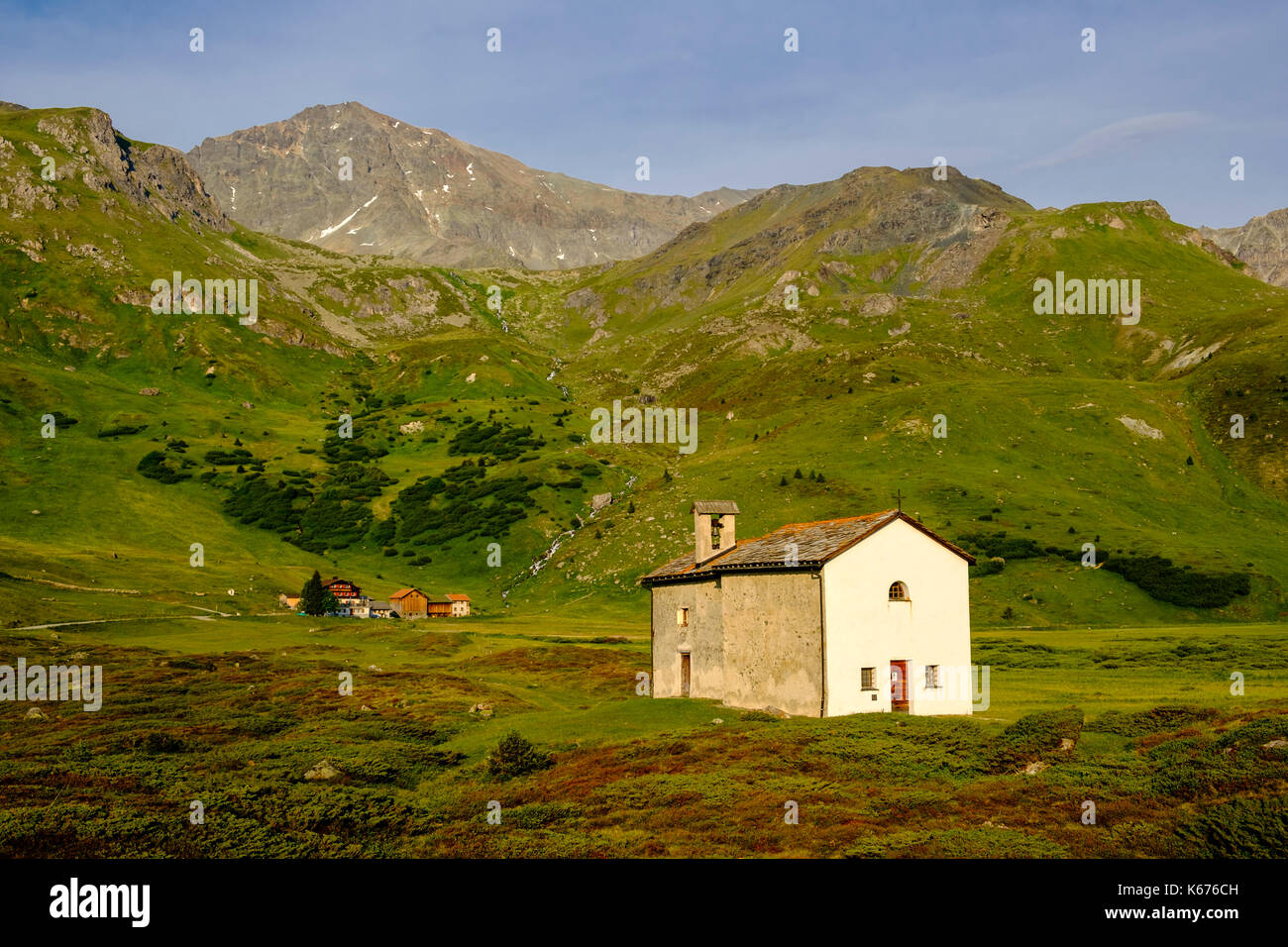 The Chapel Sun Roc, green meadows, bushes, farmhouses and mountain slopes at Alp Flix - Stock Image