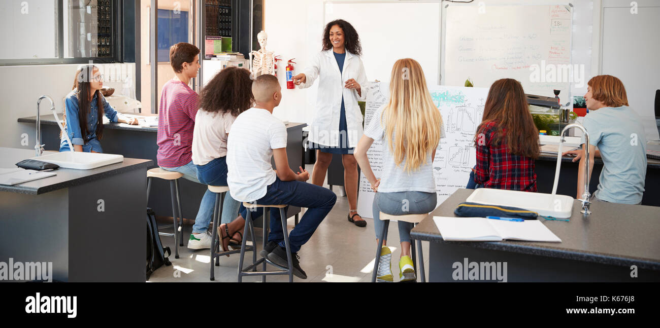 Science teacher giving presentation in school science class - Stock Image