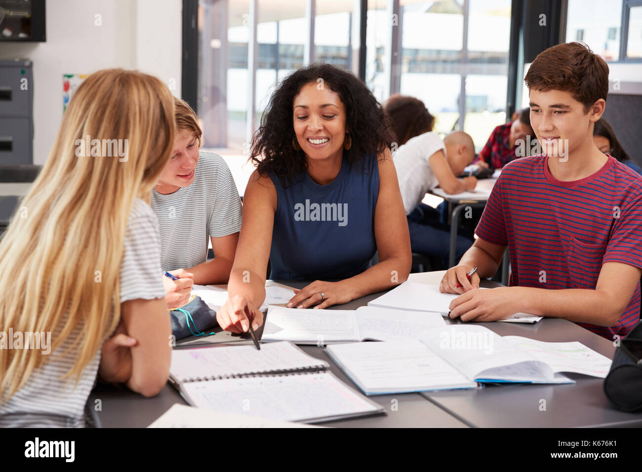 Teacher studying school books in class with high school kids - Stock Image