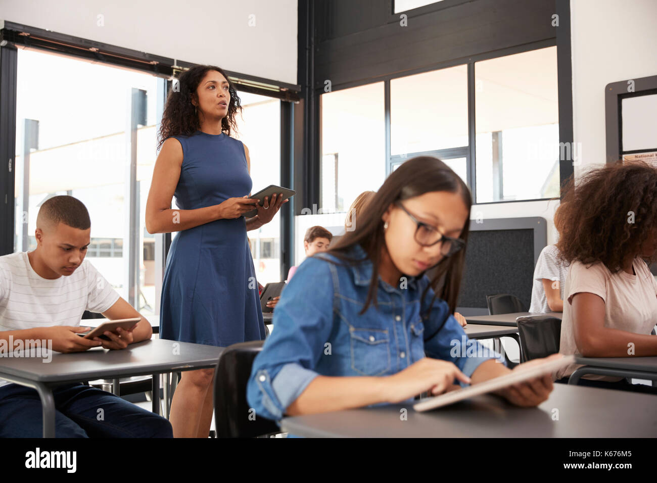 Teacher standing in the middle of her high school class - Stock Image