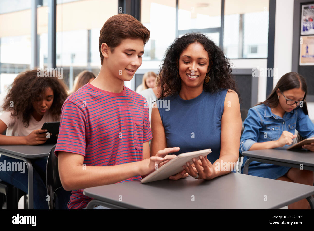 Teacher helping teenage schoolboy with tablet computer - Stock Image
