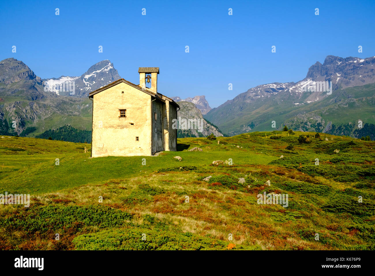 The Chapel Sun Roc, green meadows, bushes and mountain slopes at Alp Flix, high mountains in the distance - Stock Image
