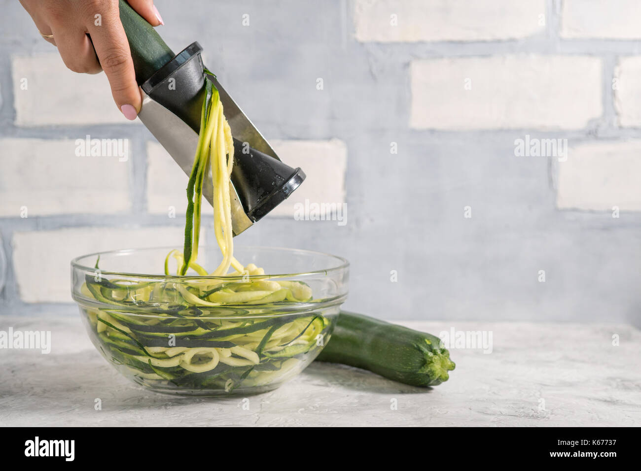Making zucchini noodles with spiralizer. Diet low carb food Stock Photo