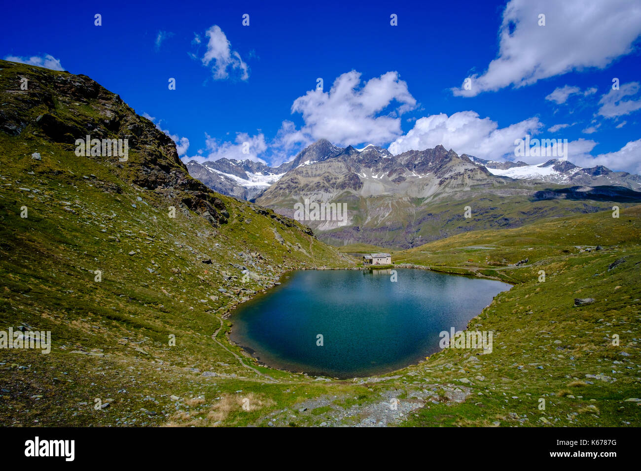 The Lake Black, Schwarzsee with the Chapel Mary of the Snows, Maria zum Schnee, high mountains in the distance - Stock Image