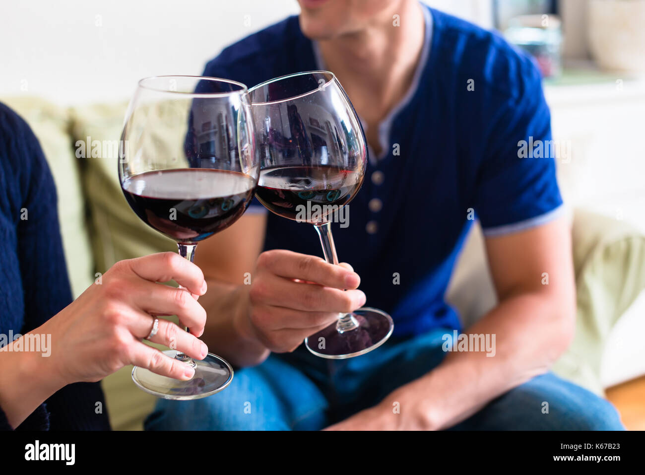 Romantic young couple toasting with red wine while sitting on th - Stock Image