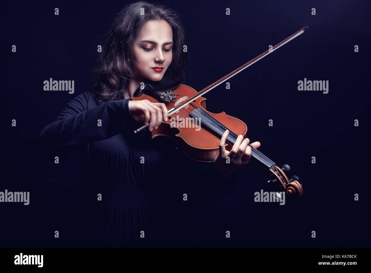 Young woman playing the violin against a dark background. Studio photo - Stock Image