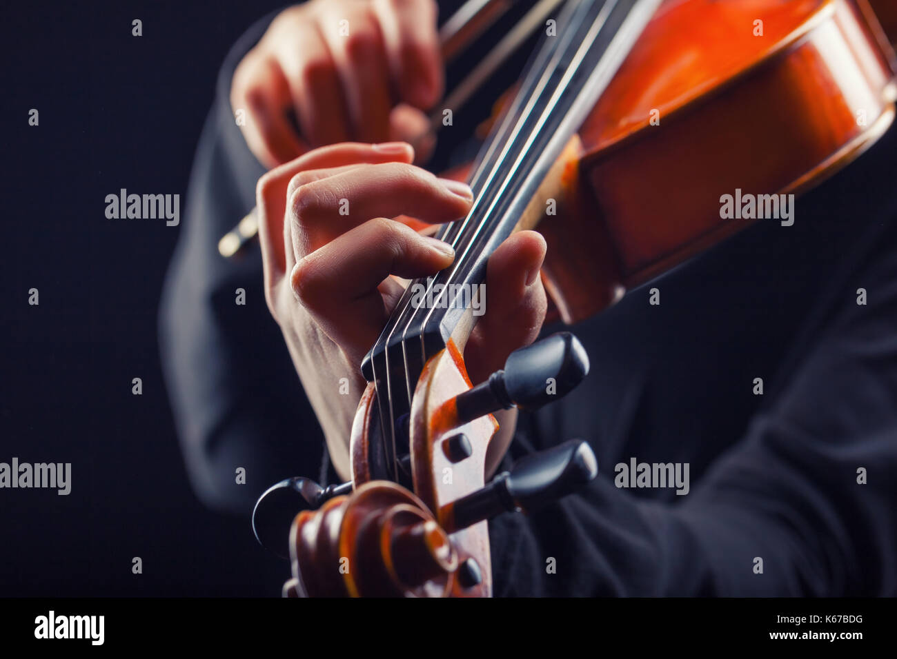 Playing the violin. Musical instrument with performer hands on dark background - Stock Image