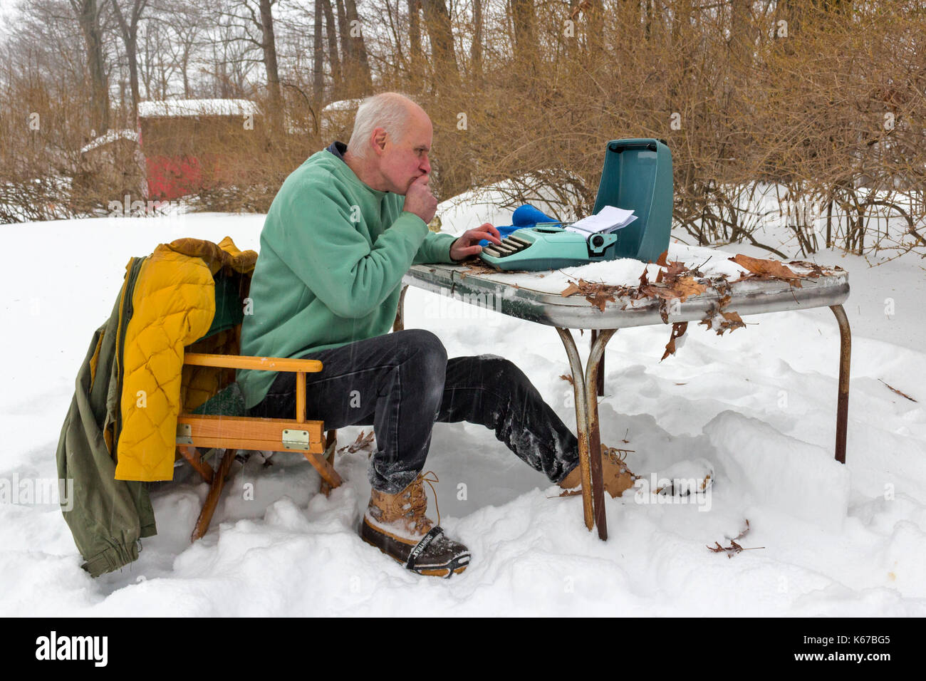 A writer sitting at a table outside during a snowstorm and typing on a typewriter. - Stock Image