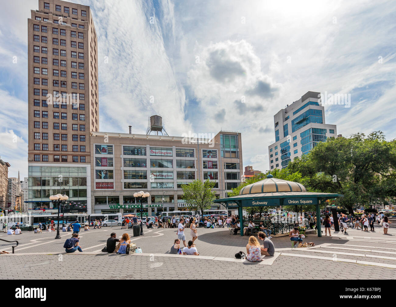 People enjoying leisure time in Union Square, New York in from of the Union Square Subway Station. - Stock Image