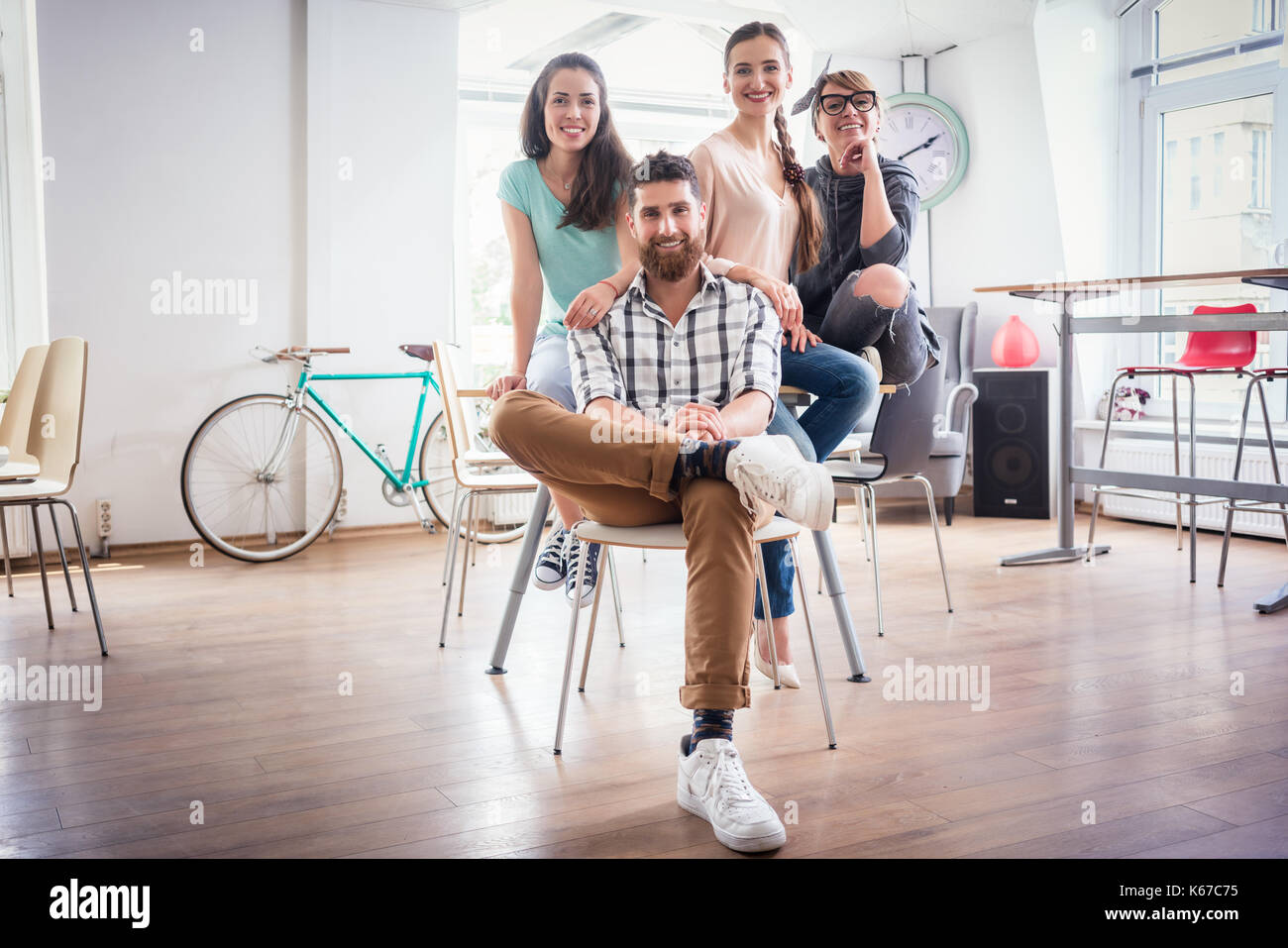four co-workers wearing casual clothes during work in a modern h - Stock Image
