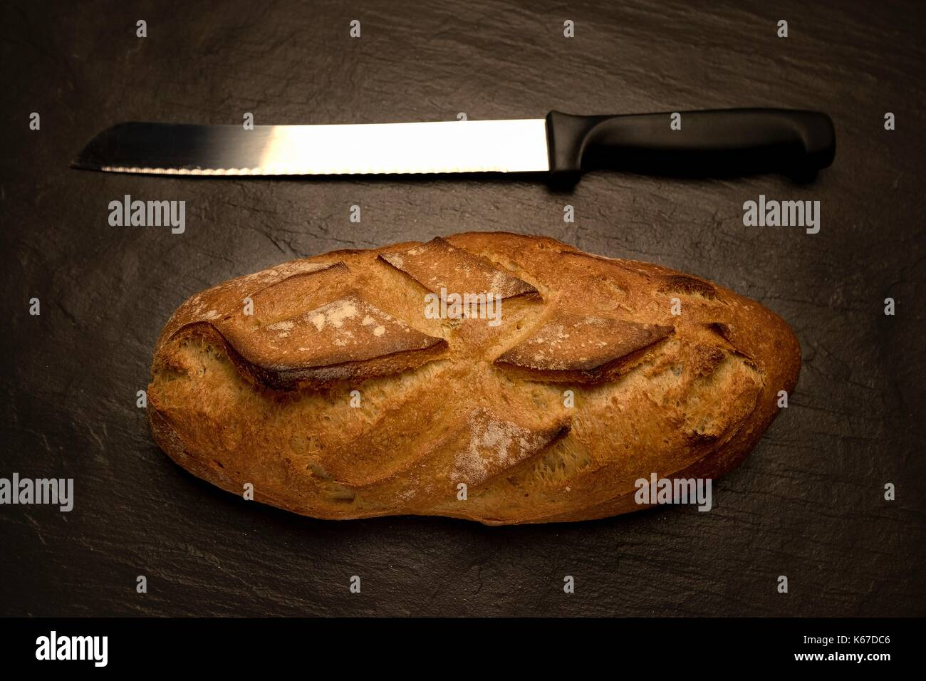 Loaf of bread with a bread knife - Stock Image