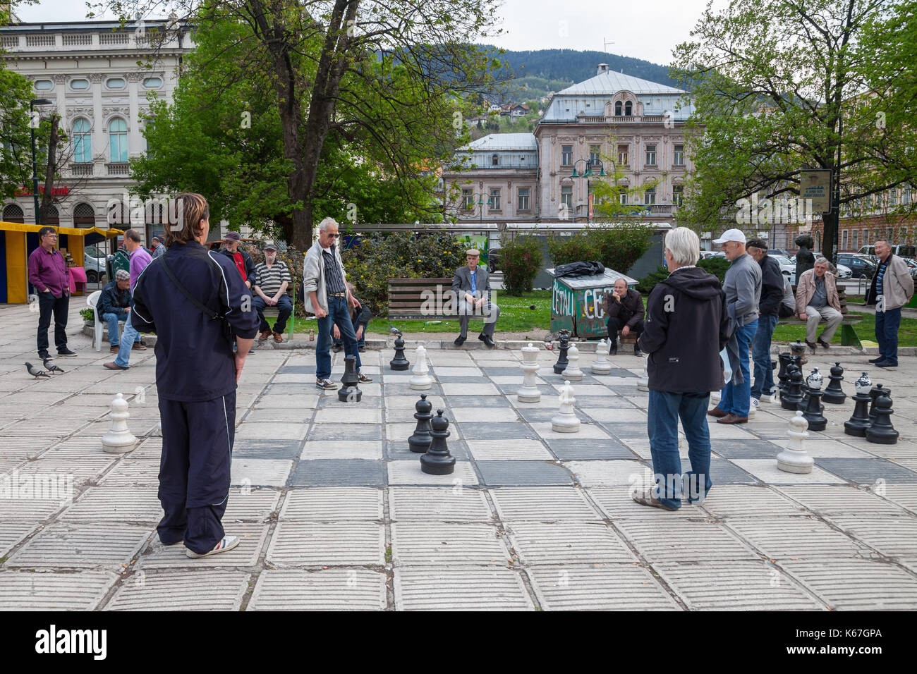 SARAJEVO, BOSNIA AND HERZEGOVINA - APRIL 15, 2017: Old men playing a giant chess game in the city center of Sarajevo, capital city of Bosnia. This che - Stock Image