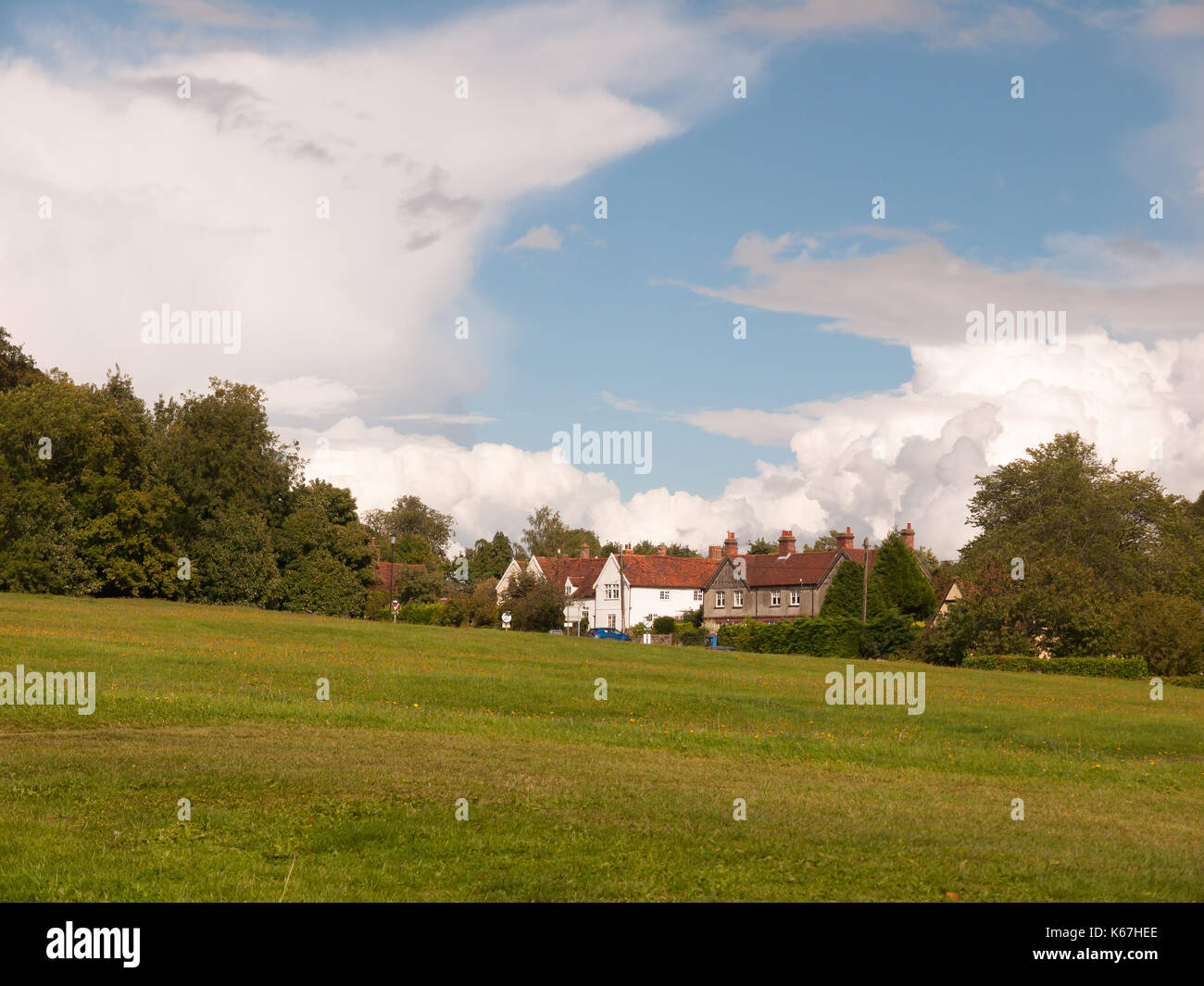 interesting sloped green lawn with country houses in background and blue and white cloud sky; England; UK - Stock Image