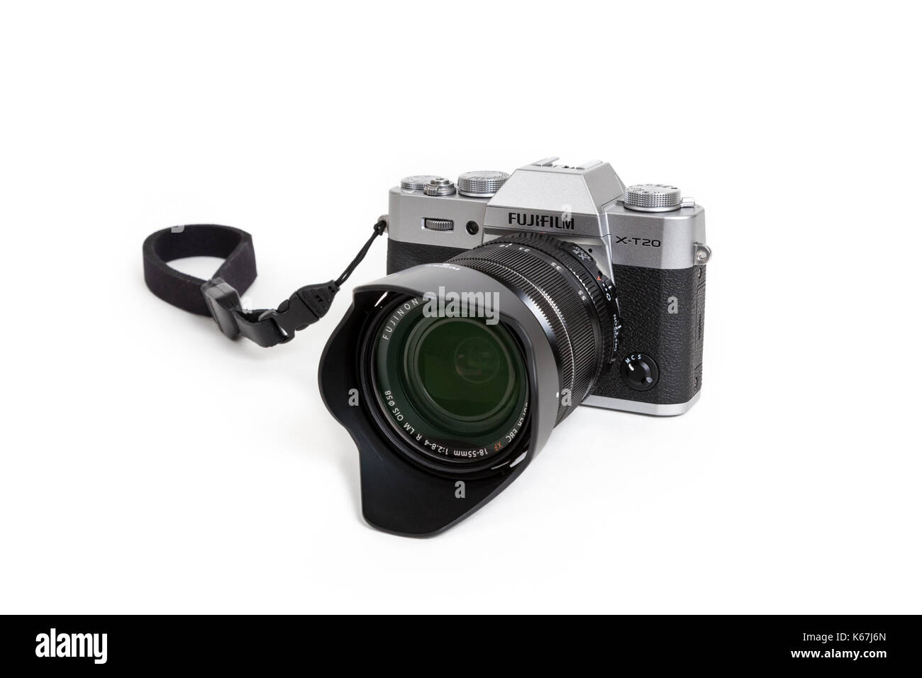 Fujifilm X-T20 mirrorless digital camera with the 18-55 mm lens, lens hood and wrist strap on a white background - Stock Image