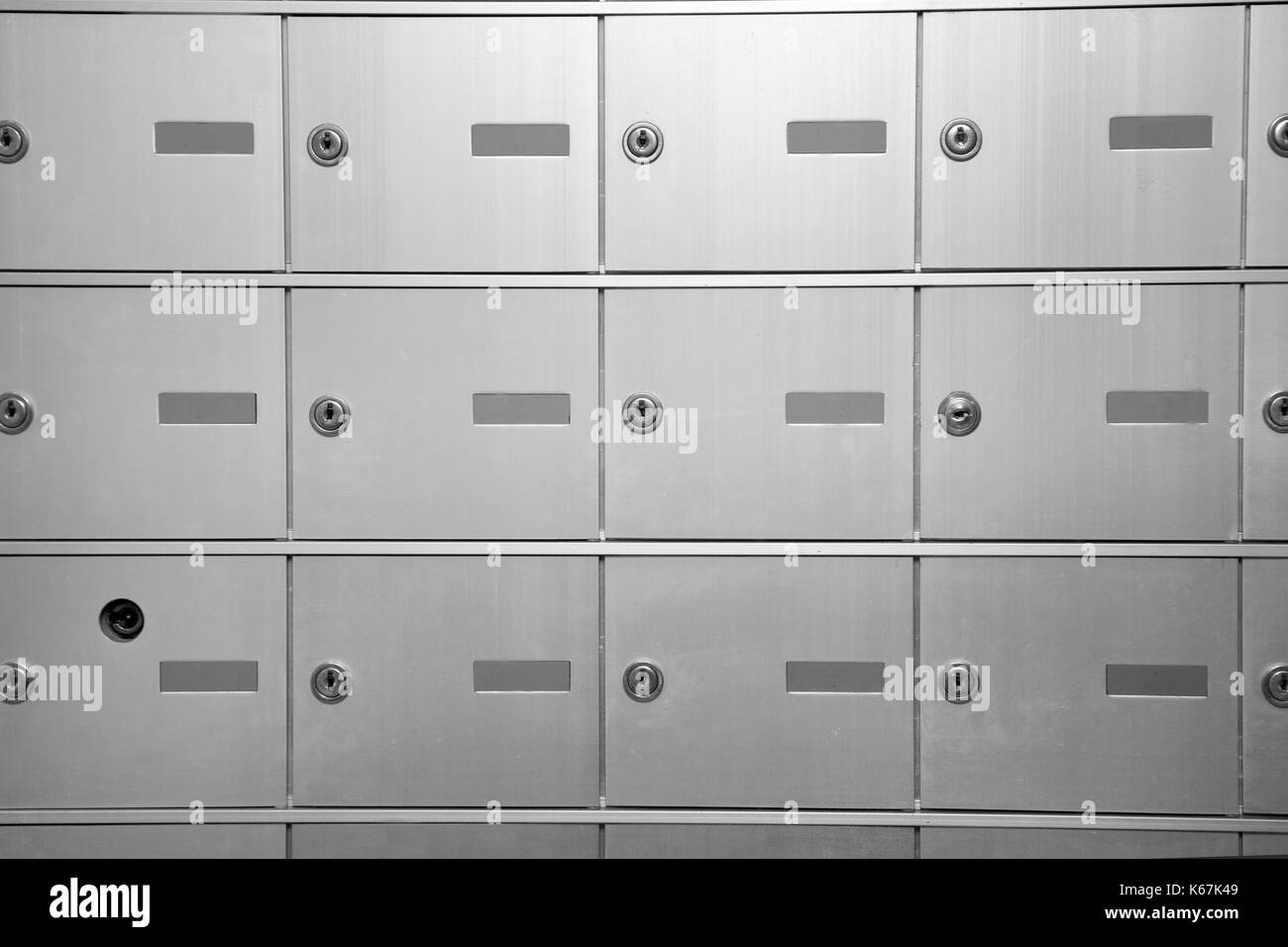 rows or grid of silver post office boxes or bank vaults with empty number plates - Stock Image