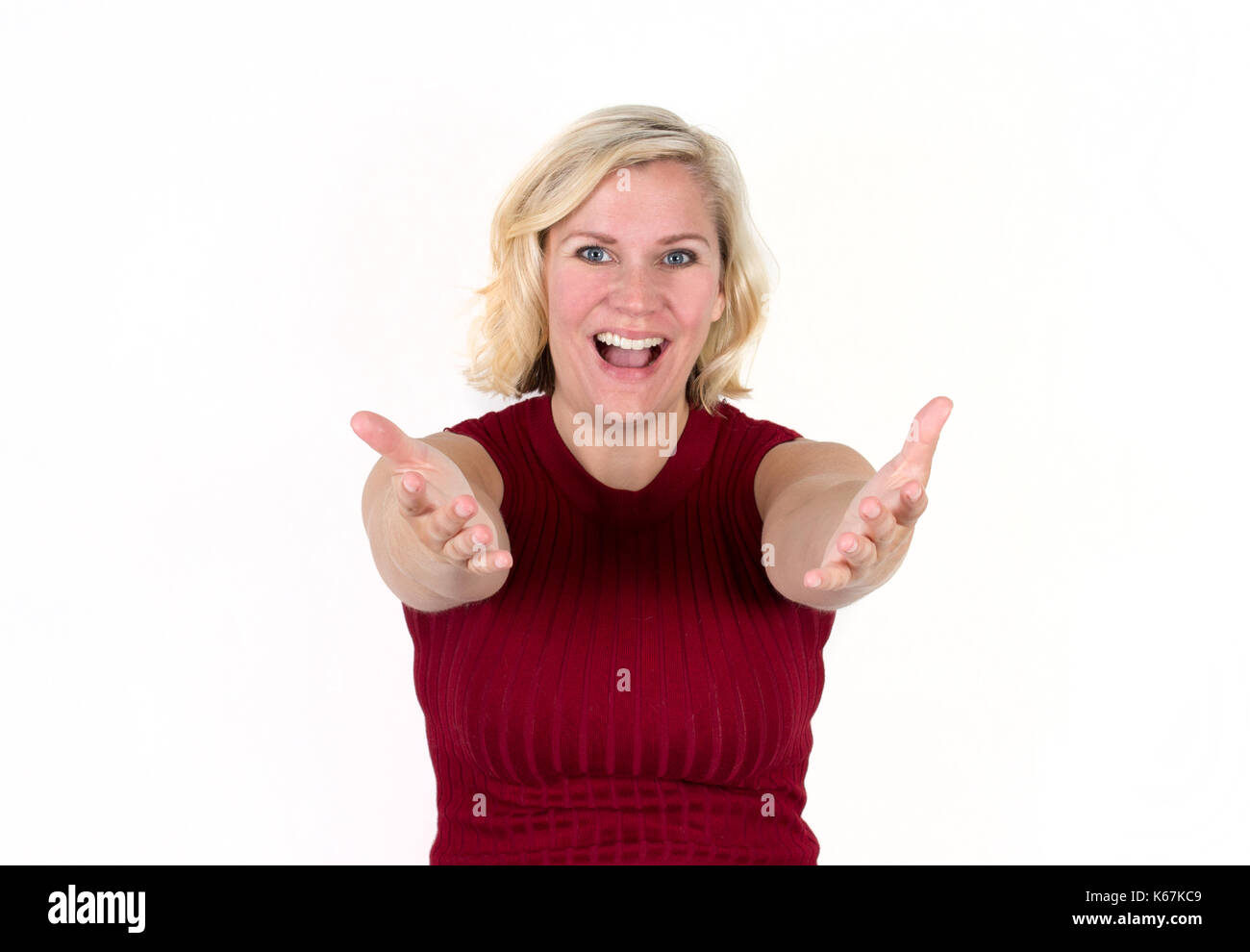 a blonde woman smiles with arms outstretched in a welcome, inviting expression - Stock Image