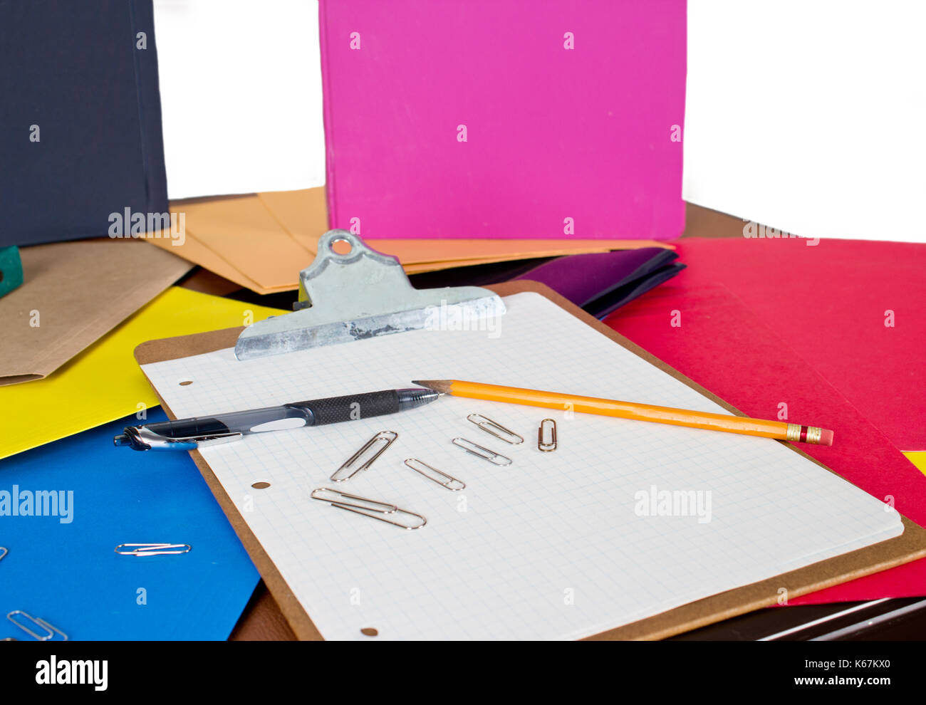 a messy desk space for back to school or office, with clipboard, pens, binders, papers, and paperclips - Stock Image