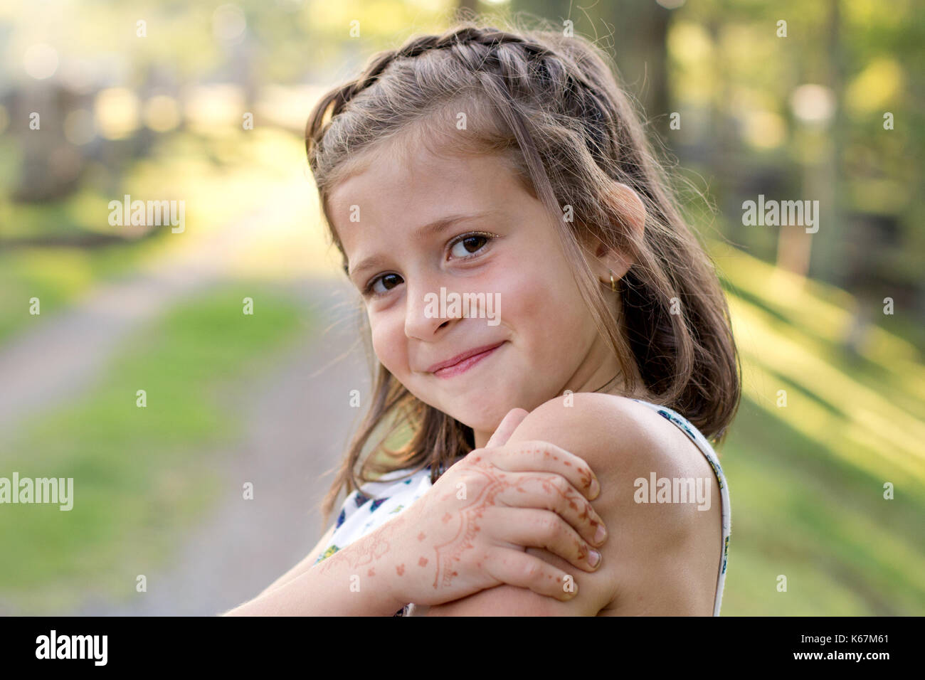 8cf48f3aa118 portrait of a smart looking young girl with a henna tattoo on her hand -  Stock